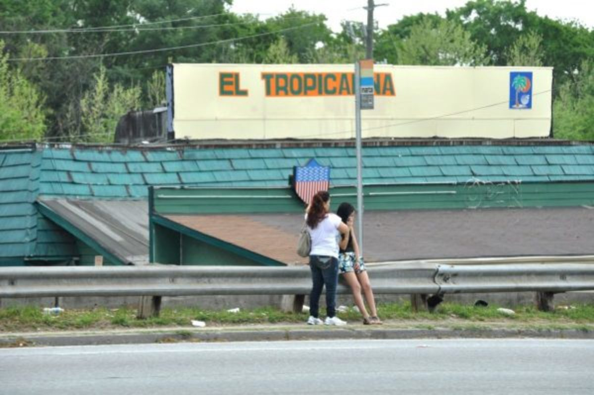 One Person standing and one person sitting talking on a phone by a bus stop infront of a sign that says El Tropicana