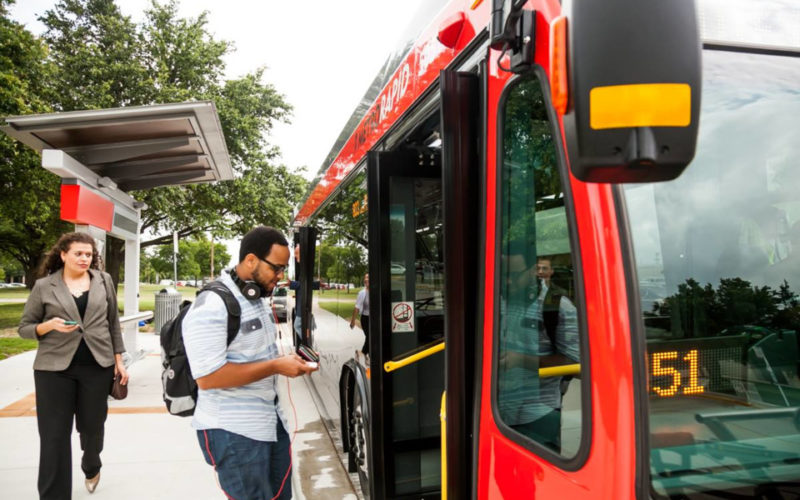 Person looking at their cell phone boardning a red bus