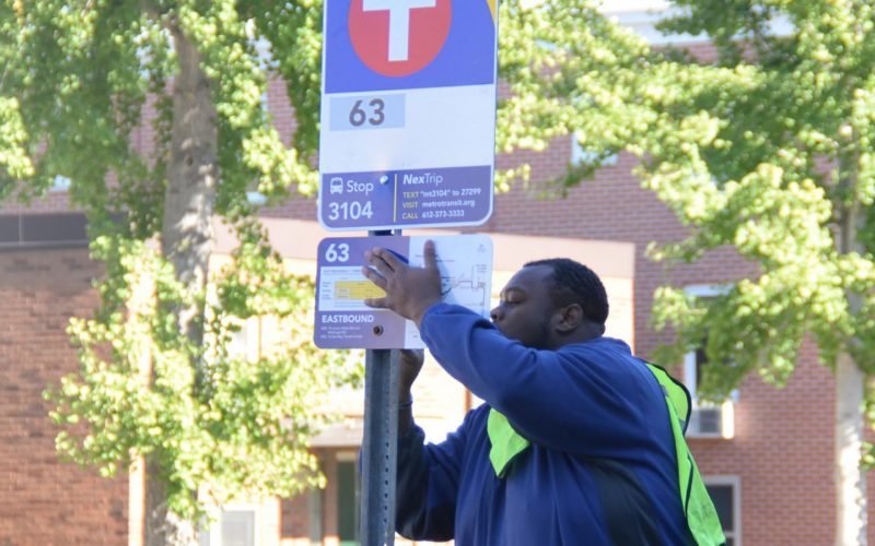Metro transit worker installing a bus sign in Minneapolis